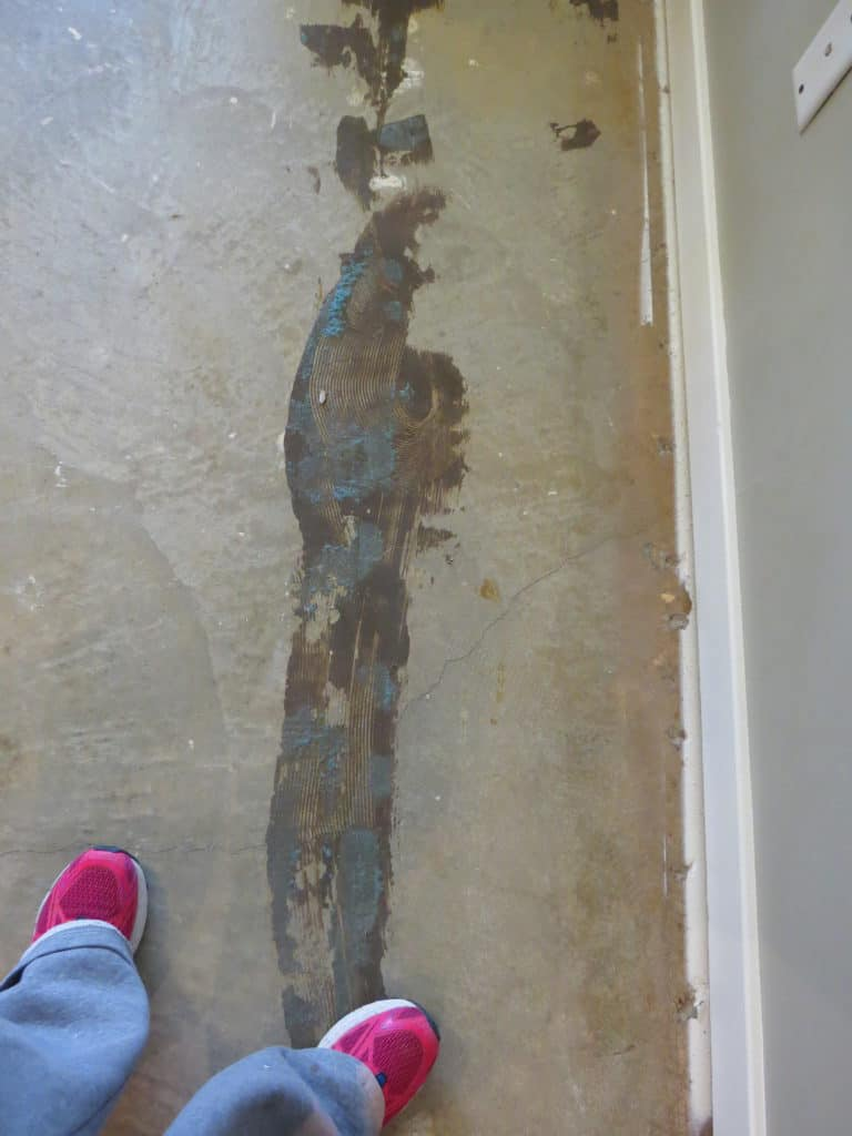 Glue residue left on the concrete floor after removing carpet padding.
