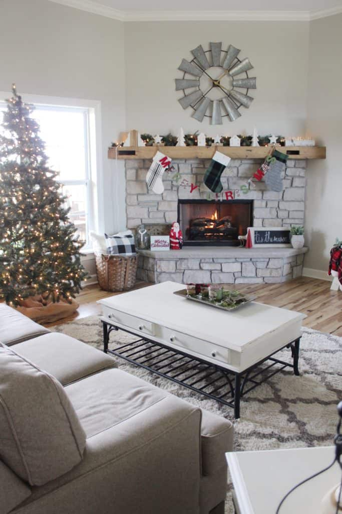 A Christmas tree with lots of lights and no ornaments next to a stone fireplace.