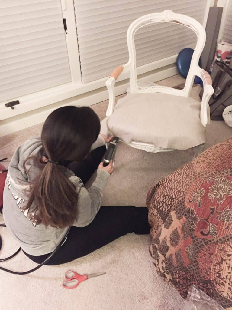 A picture of me reupholstering the seat of the French chair.