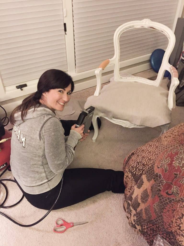 A photo of me reupholstering the seat of the French chair.