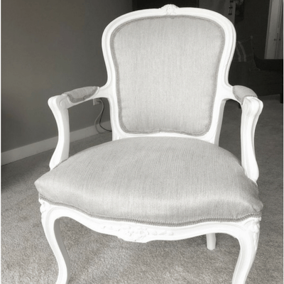 French Chair with gray fabric and white wood.