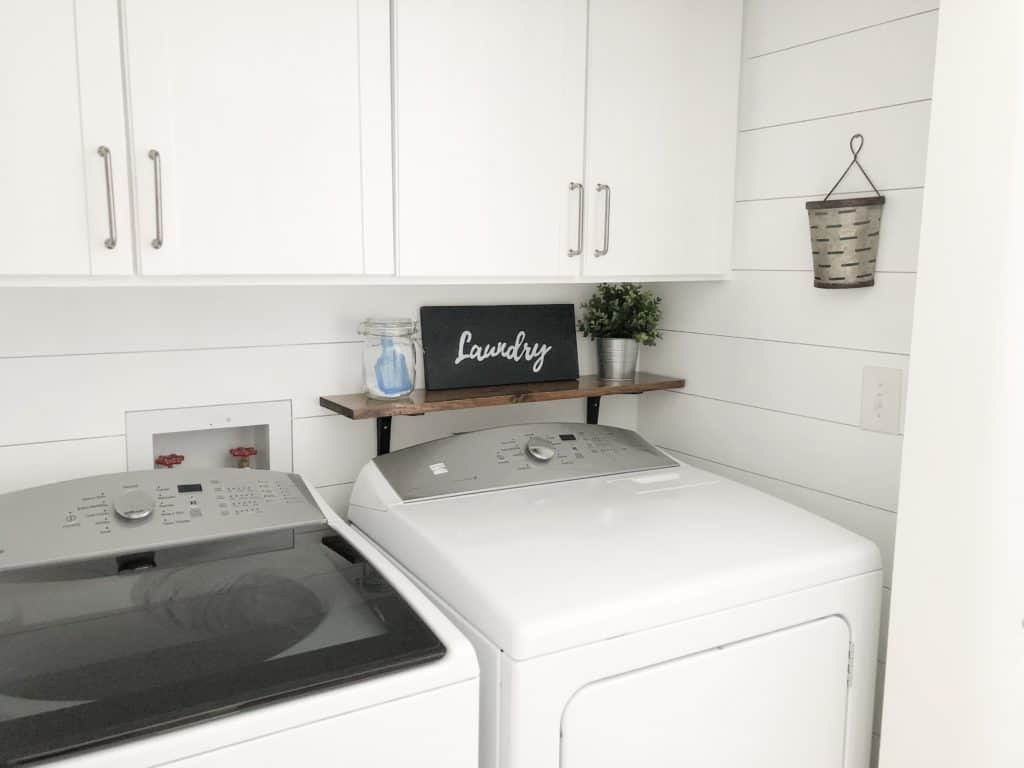 Laundry room with shiplap walls and farmhouse style decor.