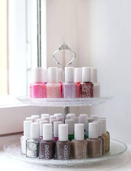 A tiered tray with pretty nail polish on it in rows.
