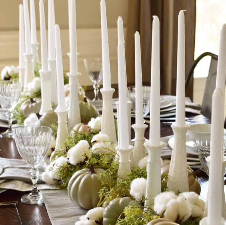 Lots of white candles down the center of a table with greenery and cotton laying in between them.