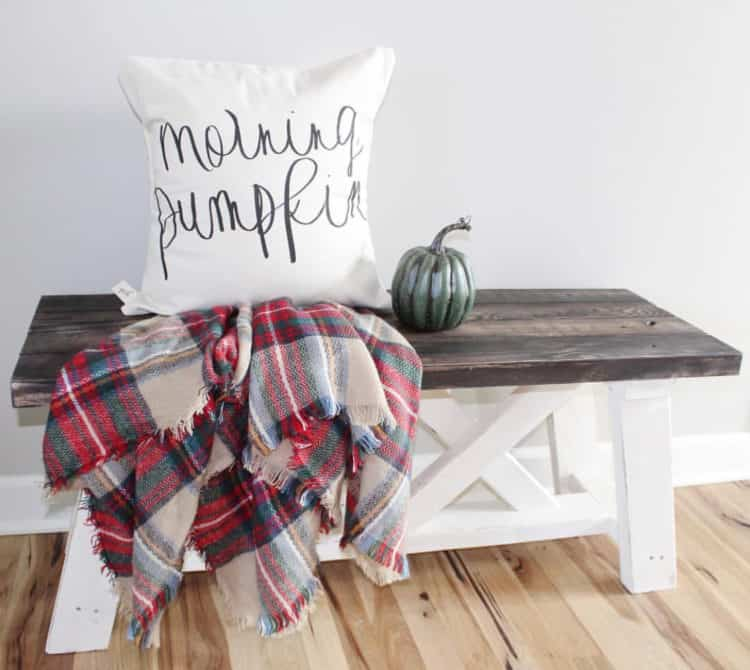 A bench with a pillow that says morning pumpkin, a blue ceramic pumpkin and a plaid scarf.
