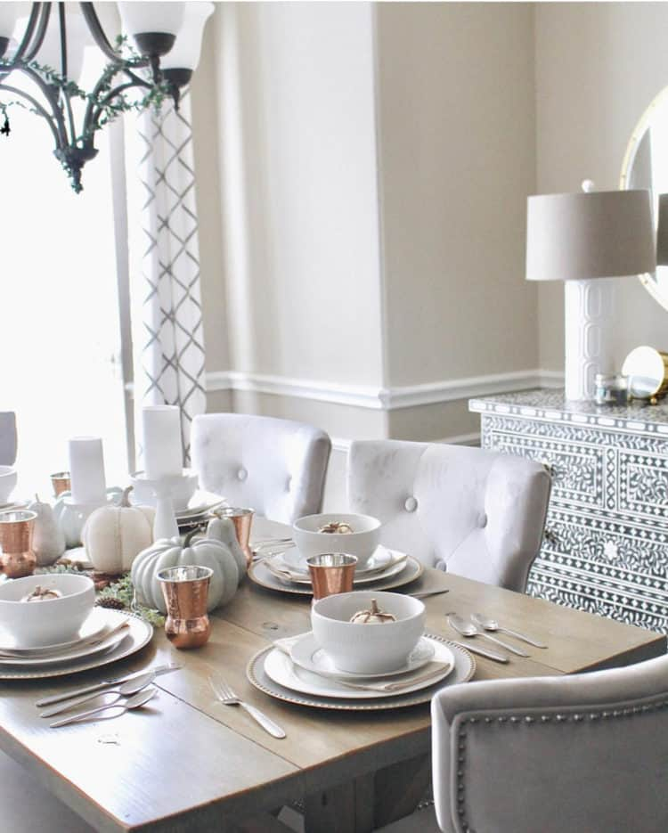 A neutral table setting with white dishes and pumpkins as well as copper cups.