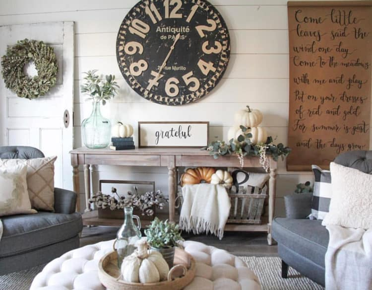 A family room with lots of neutral pumpkins, greenery and a grateful sign.