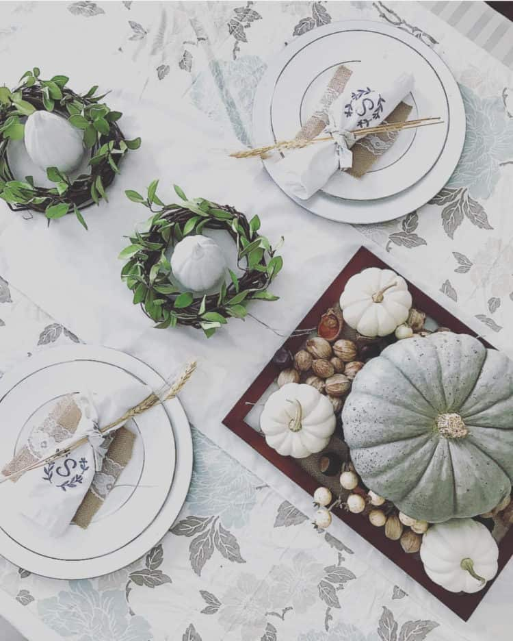 A table setting with white table cloth, neutral pumpkins and small green wreaths as a centerpiece around the pumpkins.