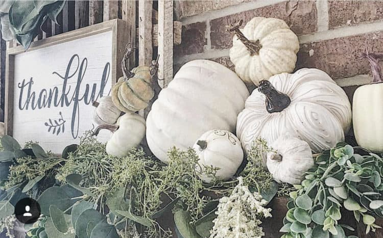 A mantel that has greenery as a base and a ton of white pumpkins on it as well as a thankful sign.