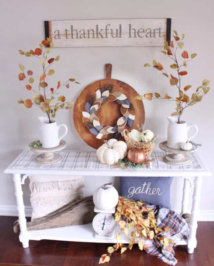 A white table that has neutral fall decor and a plaid flannel.