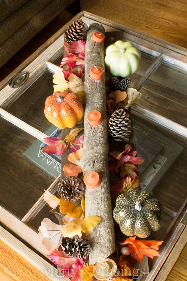 A tree branch with holes drilled into it for candles on a table surrounded by pumpkins, leaves and pinecones.