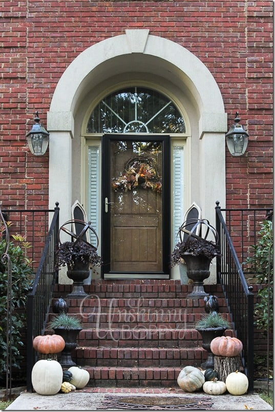 A brick stoop with neutral colored pumpkins sitting on the steps.
