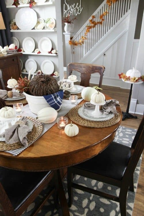 A table setting using white dishes and cream colored pumpkins.