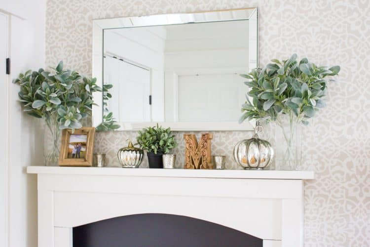 A white fireplace mantel with silver pumpkins on it and lambs ear greenery.