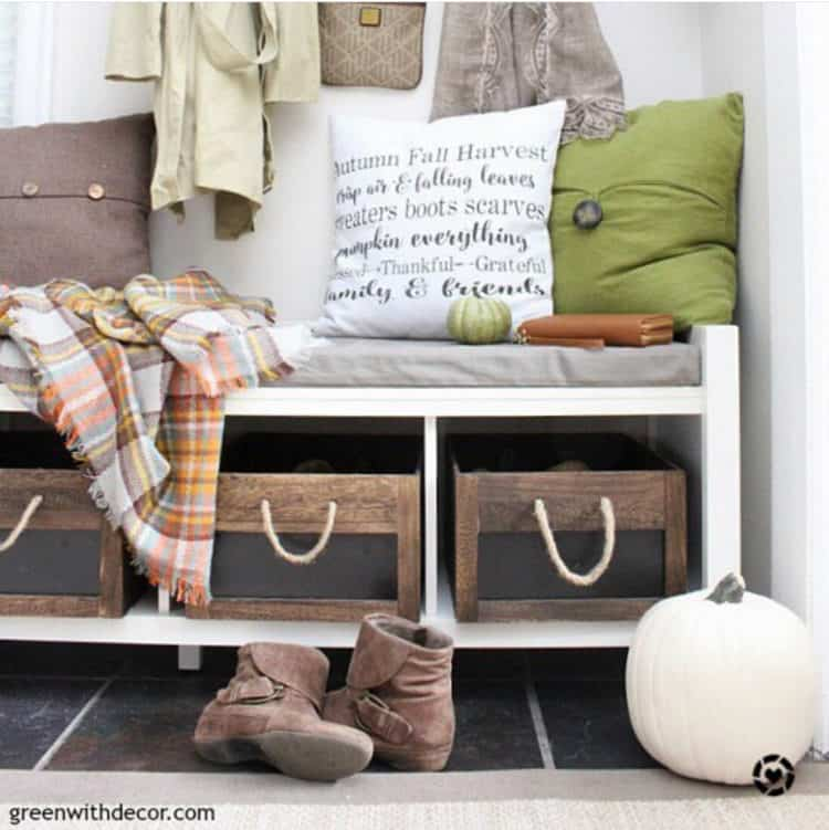 An entry bench with colorful fall pillows, a plaid scarf and brown booties on the floor in front.
