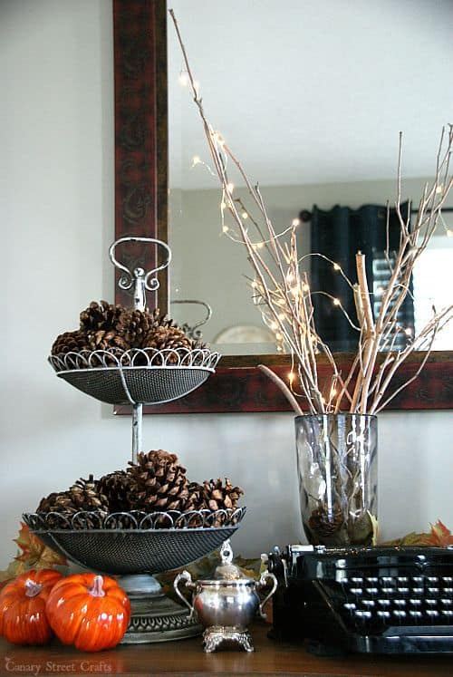 A tiered tray with pinecones in it next to a vase that has tree branches and fairy lights in it.