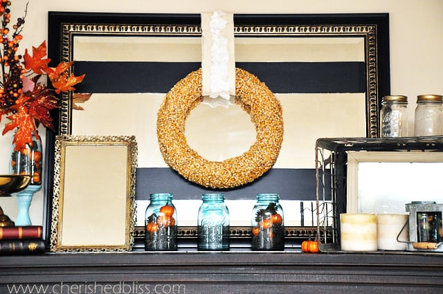 A mirror on a mantel with a wreath hanging on it made of corn kernels.