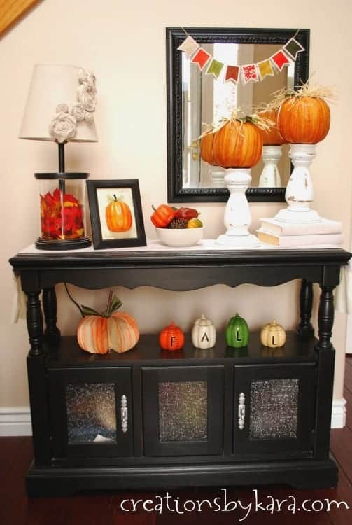 An entry table with lots of orange pumpkins.