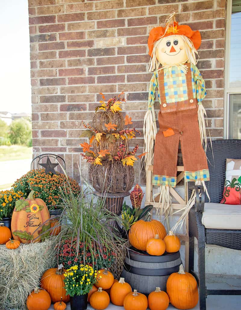 A front porch with a scarecrow, orange leaves and pumpkins and mums in baskets.