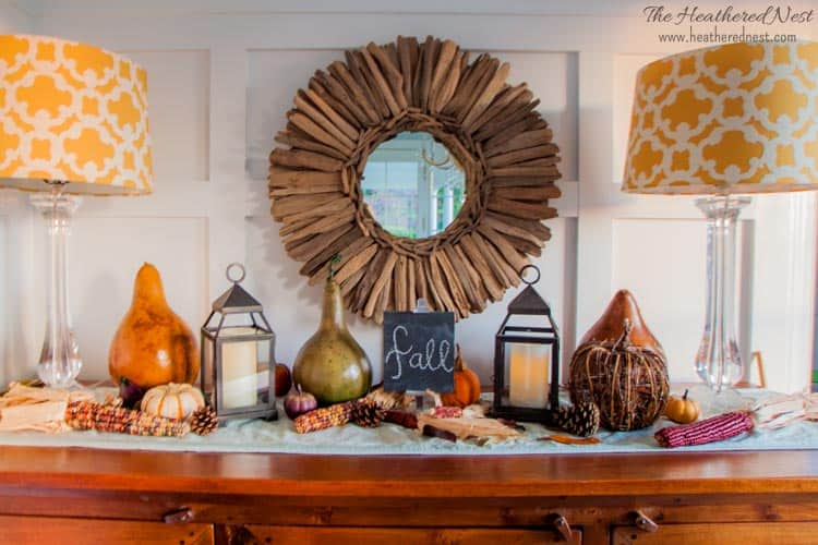 A table featuring colorful pumpkins, gourds and indian corn.  There are two lamps flanking the wreath on the wall.