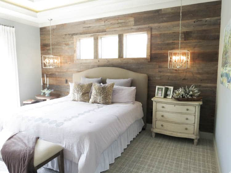 A bedroom with a wood wall on the headboard wall.