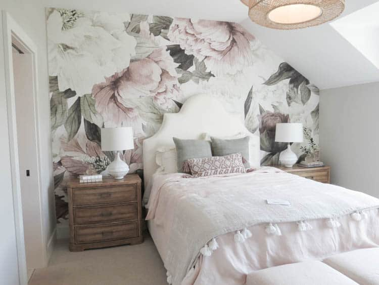 A girls bedroom with a floral mural on the headboard wall.