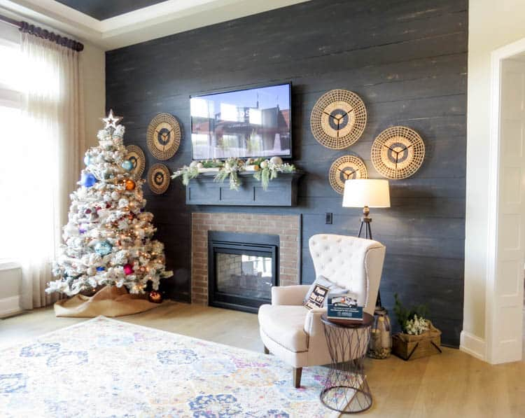 A family room with shiplap on the wall with a fireplace and it's painted black.