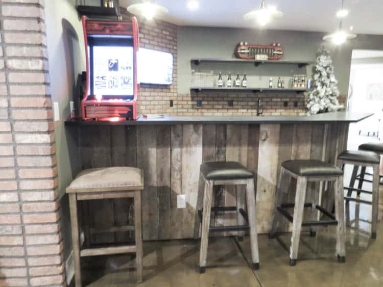 A bar in the home with wood on the bar counter and brick on the wall.