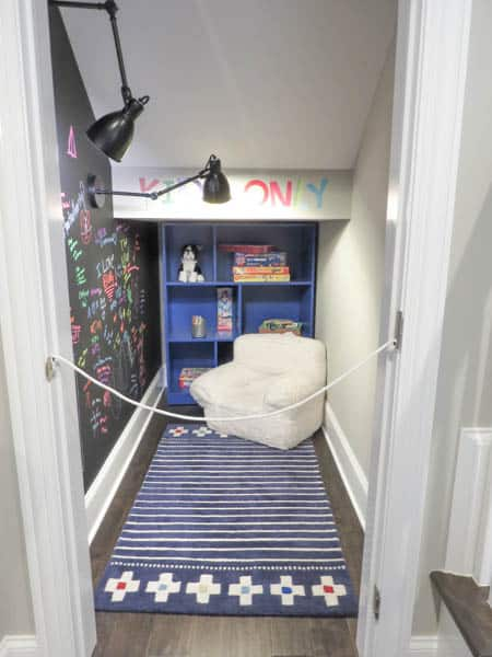 A nook under the stairs with a chalkboard accent wall.