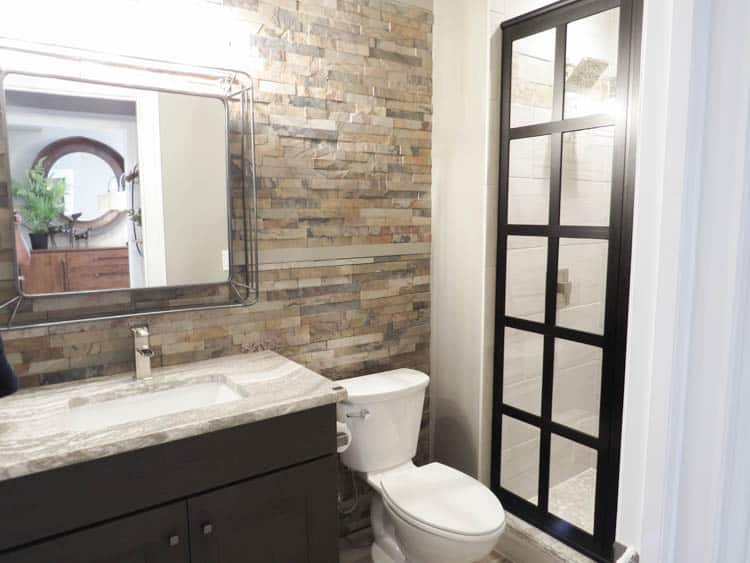A bathroom with stacked stone tile on the wall behind the vanity.