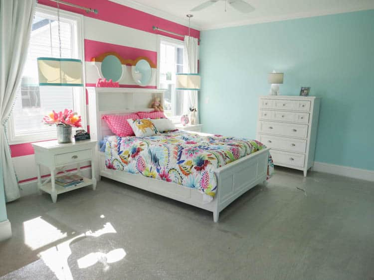 A girls bedroom with light blue walls and an accent wall with pink and white stripes.
