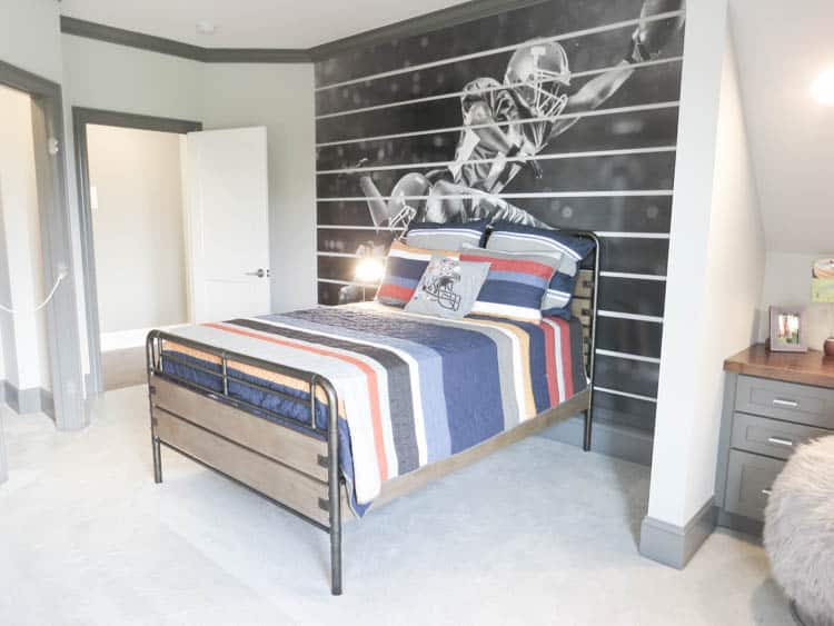 A headboard wall with a mural of a football player in black and white.