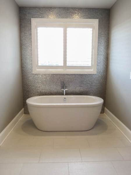 A free standing tub with a shiny tile wall behind it with a window.