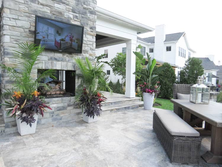 A patio with a fireplace and a tv above it with gorgeous planters.