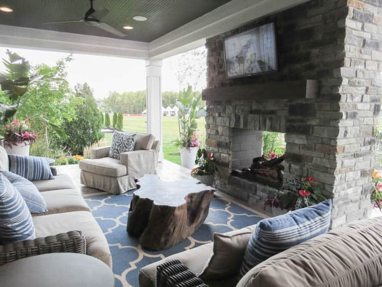 An outdoor patio that is covered. There are sofas and a fireplace with a tv.