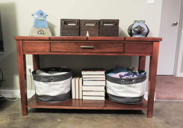 A sofa table in a redish brown color with books and baskets on the bottom and baskets with pottery on the top.
