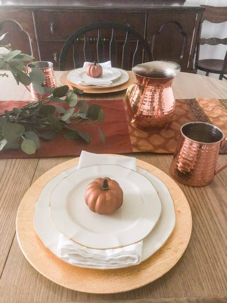 Gold chargers with ivory dishes, white napkin and a copper pumpkin on top.