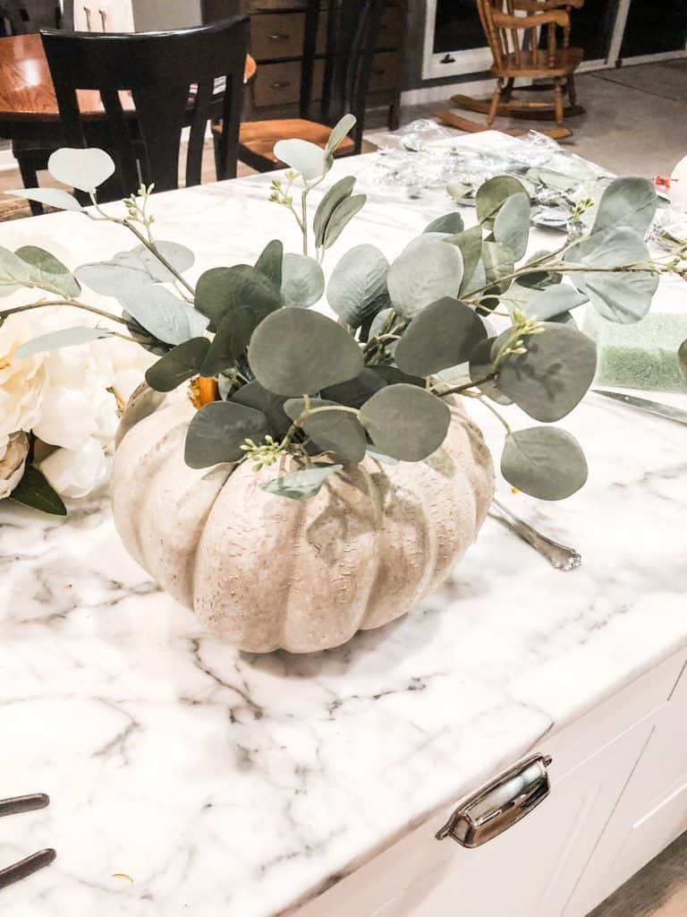 adding the eucalyptus to the pumpkin floral arrangement