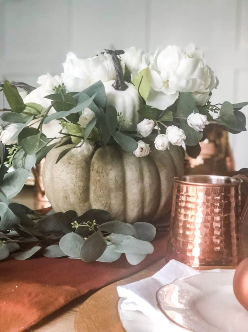 A close up of the pumpkin flower arrangement and the copper mugs.