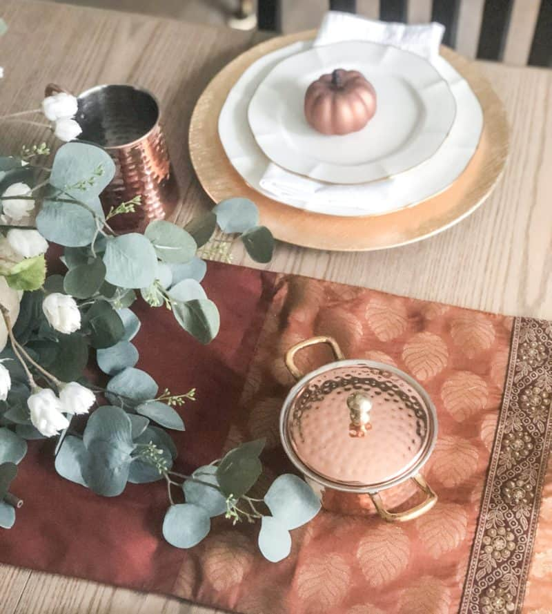 Copper dishes on a fall table runner.
