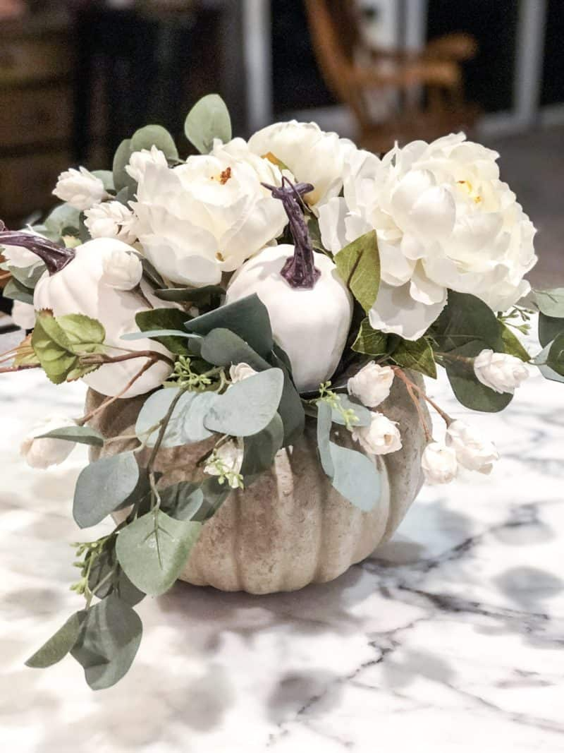 A pumpkin flower arrangement with small white flowers, white peonies and eucalyptus.
