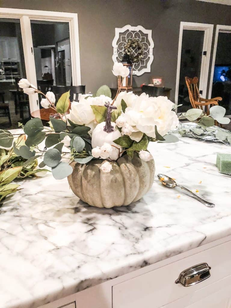 Adding little white flowers to drape over the edges of the pumpkin flower arrangement.