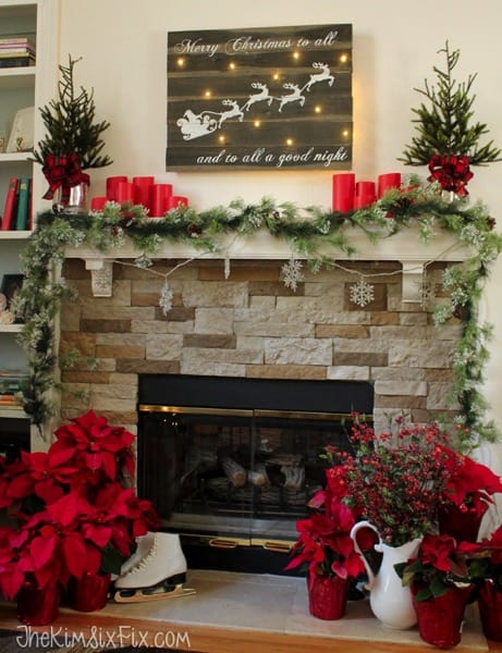 Mantel Decorations for Christmas, lighted sign above mantel of Santa flying iwht reindeer, on the mantel are red candles and flanking are two small christmas trees. garland and poinsettias too