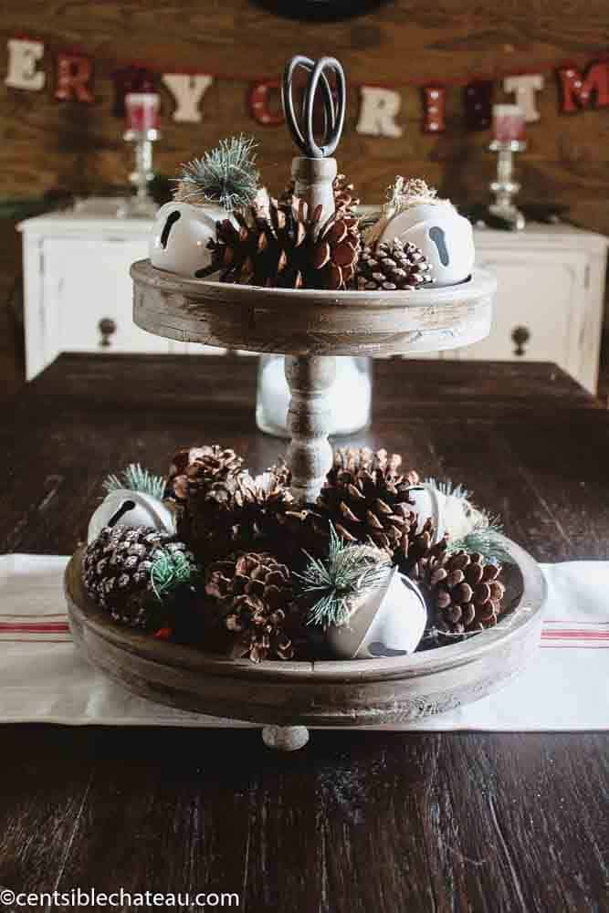 Farmhouse Christmas decor a tiered tray with pinecones and sleigh bells on it.