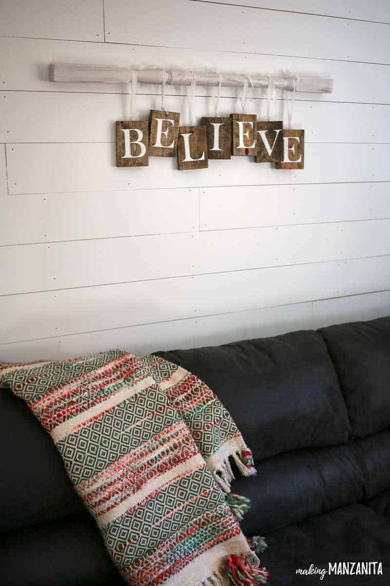 Farmhouse Christmas Decor, a Believe sign hanging on a spindle above a couch