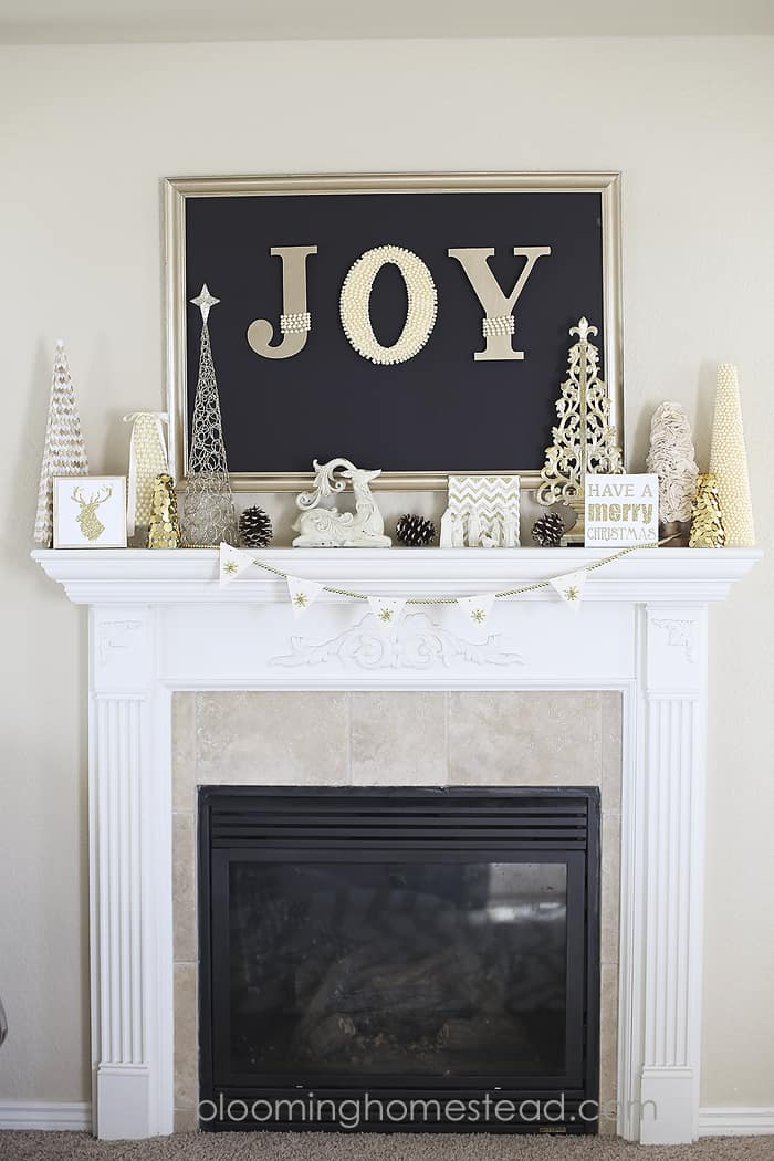 Mantel decorations for Christmas, white fireplace with a large joy sign and gold and white decor