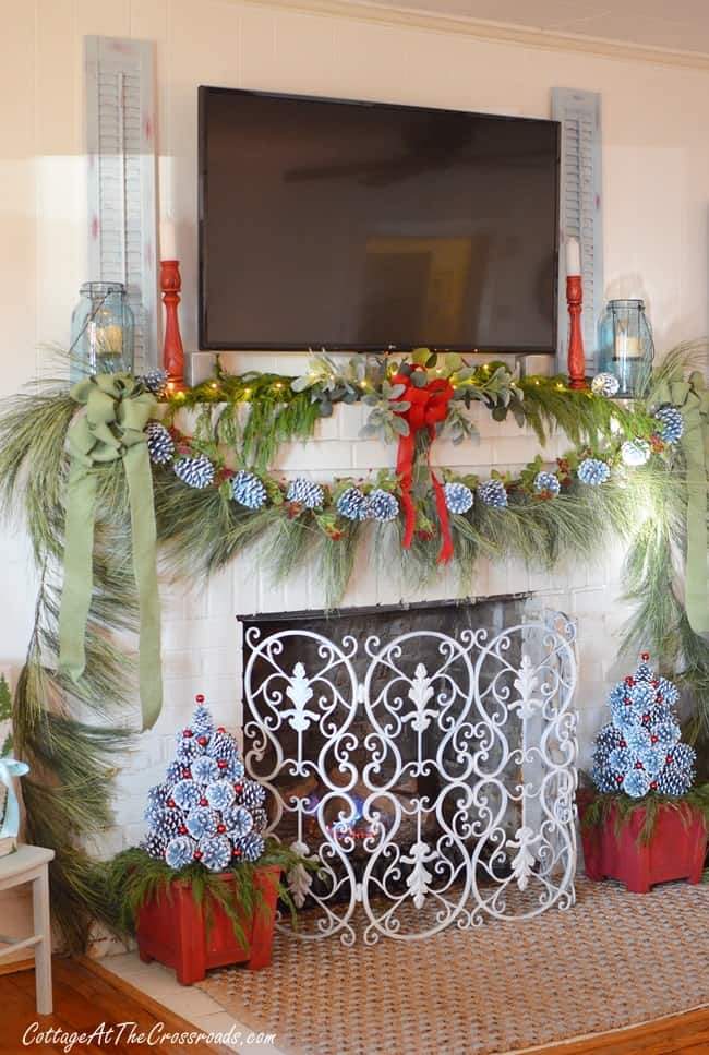 Mantel Decorations for Christmas, decorating around a christmas tree with a beautiful garland, lots of pinecones and red decor