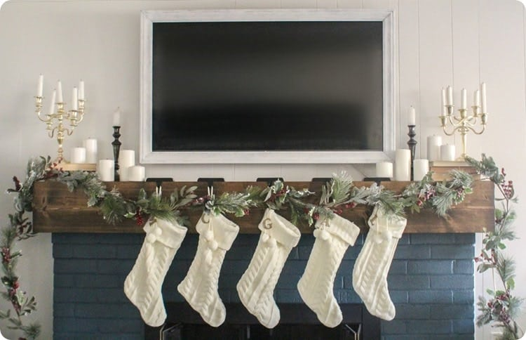 mantel decorations for christmas a tv above the mantel, garland and white knit stockings with white decor