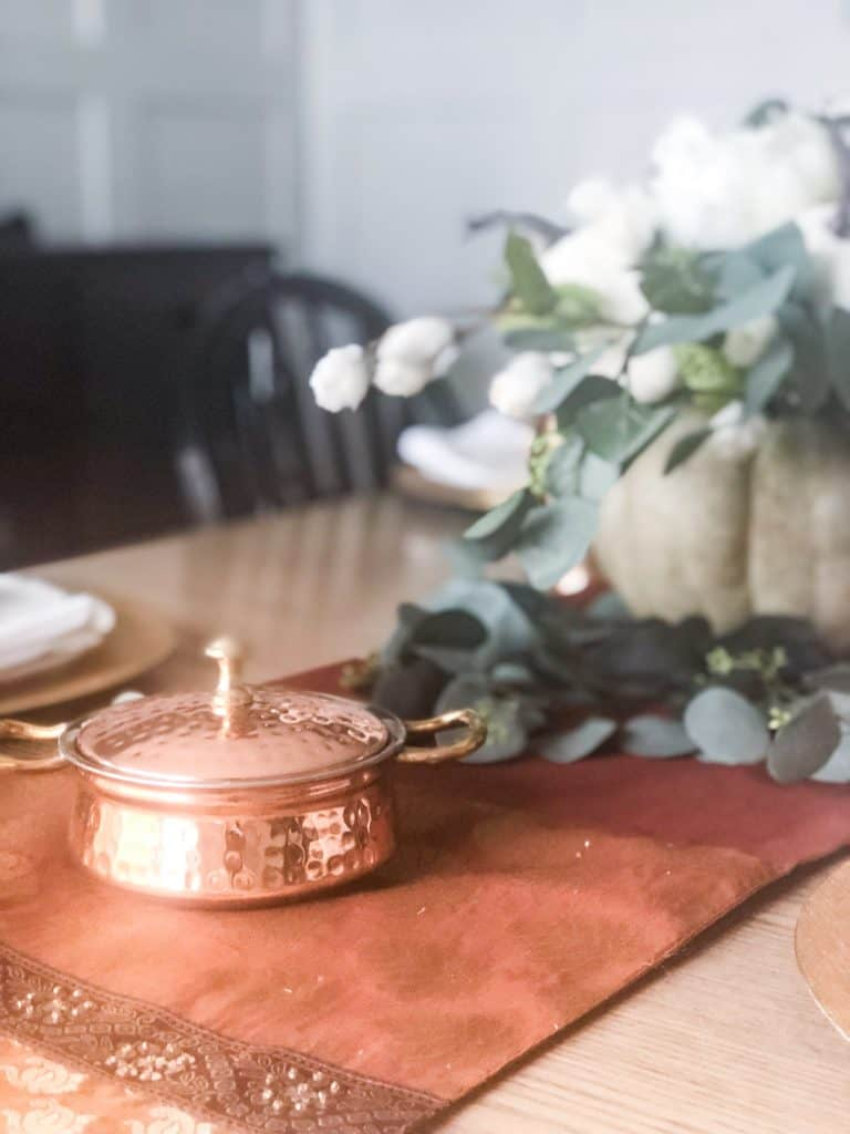 A copper dish on a copper and gold runner next to a pumpkin flower arrangement.