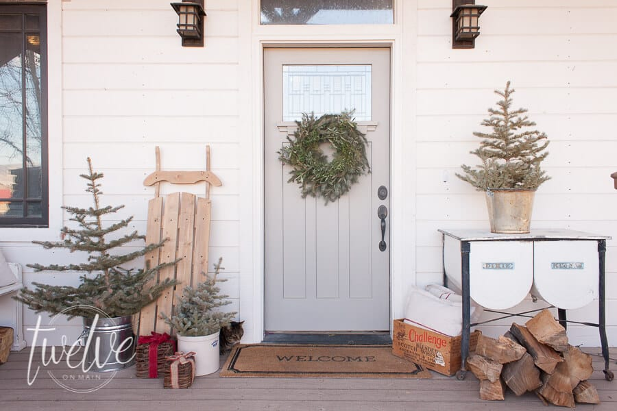 Farmhouse Christmas Decor a beautiful front porch with a sled, wood for a fire and small christmas trees.